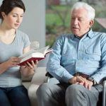 Home aide reading to elderly man