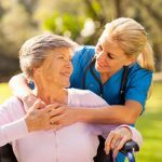Home aide with elderly woman outdoors