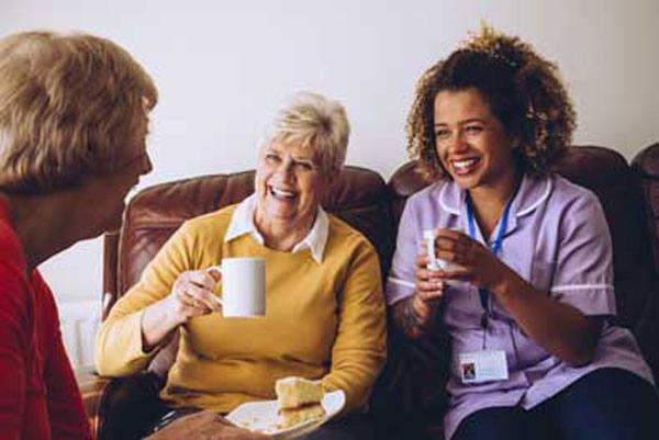 Home care aide socializing with elderly women