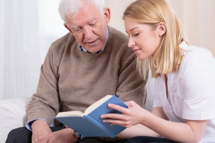 Home aide reading with elderly man