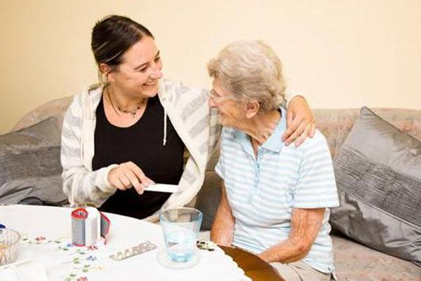Home aide assisting elderly woman
